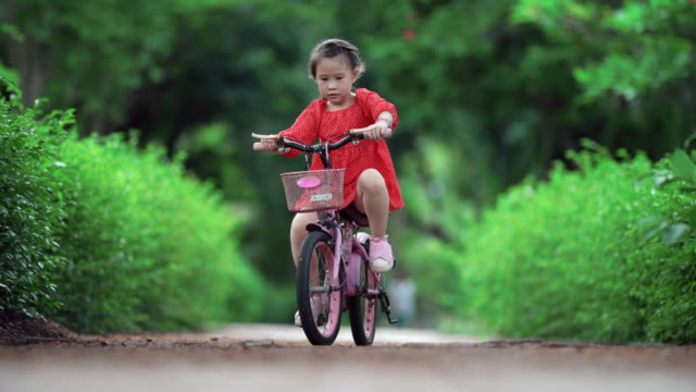children girl are cycling in public park - healthy lifestyle stock videos & royalty-free footage