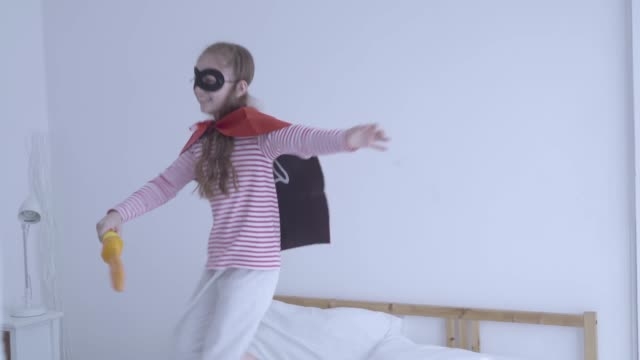 Children girl cosplay hero Jumping On Bed.