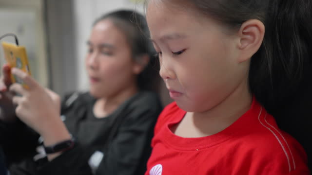 children girl playing game multiplayer on smartphone - catching stock videos & royalty-free footage
