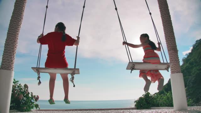 vídeos de stock e filmes b-roll de slo mo children girl playing swing on the beach - família com dois filhos