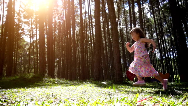 Children girl running in pine forest, Slow motion shot