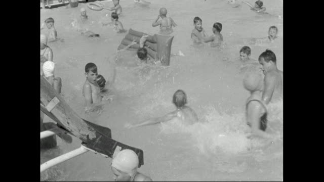 children go down slide into pool; 1959 - water slide stock videos & royalty-free footage