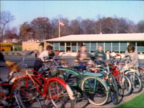 vídeos y material grabado en eventos de stock de 1957 children grabbing bicycles outside of school building + riding away / new jersey / industrial - bicicleta vintage