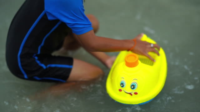 ビーチでボートのおもちゃを遊ぶ子供たちの手 - 小型船舶点の映像素材/bロール