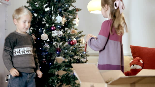 Children hang decorations on christmas tree