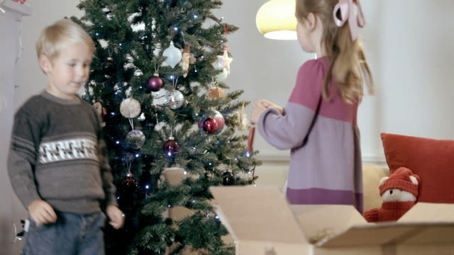 children hang decorations on christmas tree - positioning stock videos and b-roll footage
