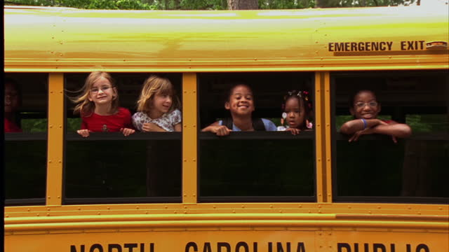 vídeos y material grabado en eventos de stock de children hang out of the windows of a school bus. - wilmington carolina del norte