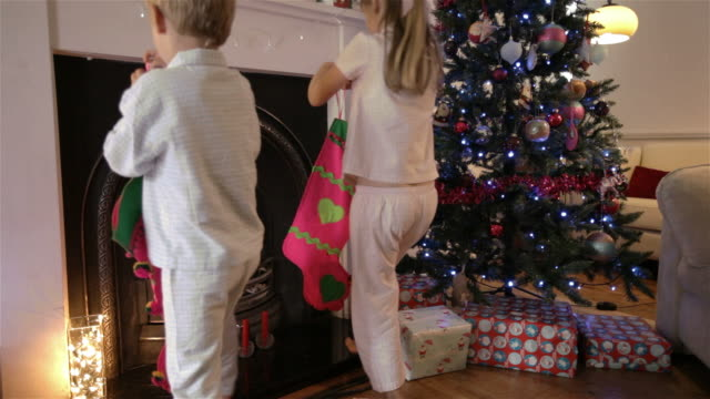 Children hanging stockings by the chimney