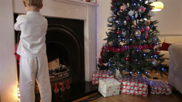children hanging their christmas stockings - stockings stock videos & royalty-free footage