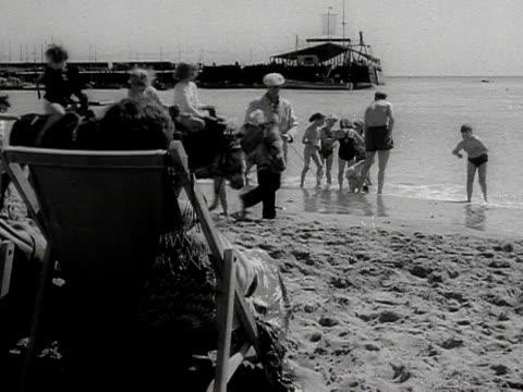 stockvideo's en b-roll-footage met children have donkey rides on beach - paardachtigen