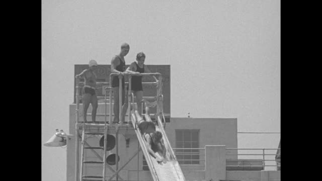 vs children have fun sliding down a metal slide / vs a small group of mostly chubby children at the edge of the pool / note exact year not known... - water slide stock videos & royalty-free footage