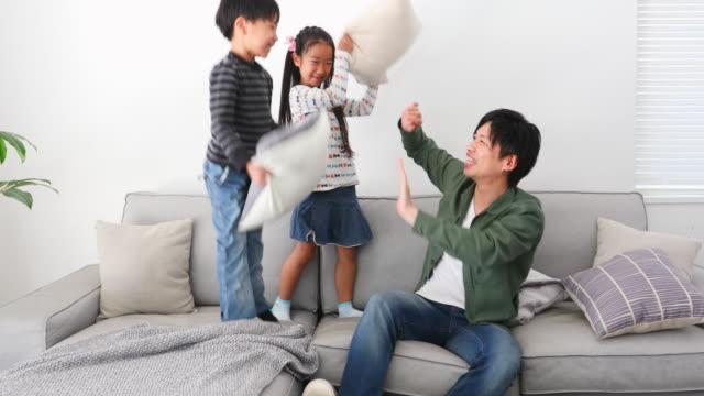 父親と枕でけんかする子供たち - 兄弟点の映像素材/bロール