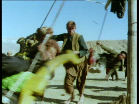 stockvideo's en b-roll-footage met children having a ride on carousel at village fair afghanistan;1975 - afghanistan