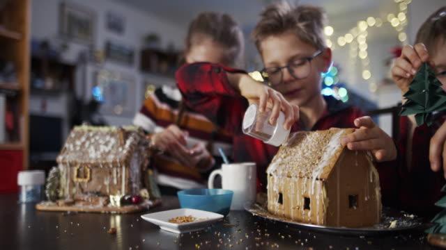 vídeos y material grabado en eventos de stock de niños divirtiéndose decorando casas de pan de jengibre - craft