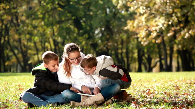 Children having fun in nature with digital tablet