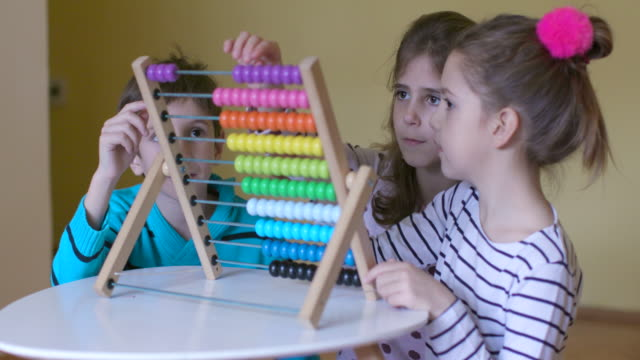 Children having fun while using abacus, slow motion