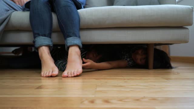 Children hidden under the sofa