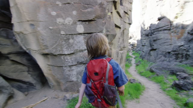 vidéos et rushes de children hike through rock canyon - découverte