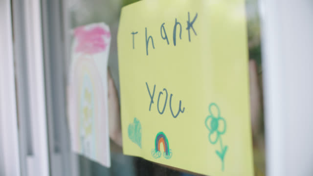 vidéos et rushes de slo mo. children hold homemade thank you signs up to window. - panneau