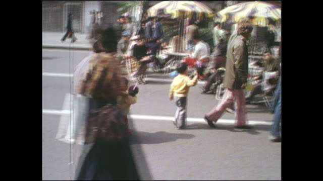 children holding dakko-chan toys cross the street with their mother as shoppers mob vendors to buy the dolls. - showa period stock videos & royalty-free footage