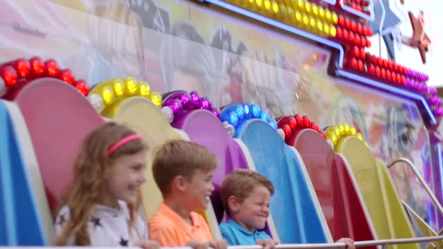children holding onto fast carnival ride - fairground ride stock videos & royalty-free footage