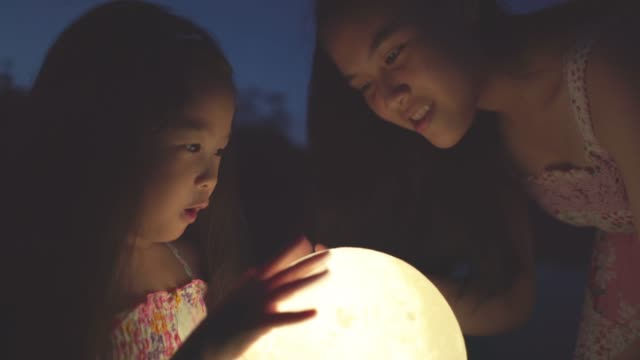 children holding the moon at night - back lit stock videos & royalty-free footage