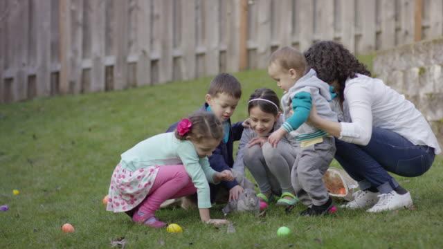 Kinder drängten rund um ein Hase