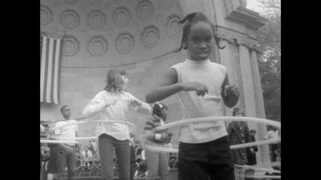 / children hula hoop outdoors in central park in front of seated audience / kids do tricks as they hula hoop hula hoop contest on october 12 1967 in... - overweight child stock videos & royalty-free footage