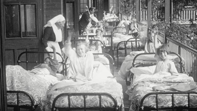 1925 MONTAGE Children in beds on open-air porch waving and large group of physically handicapped children taking a walk on the sidewalk running along the porch / Newcastle upon Tyne, England, United Kingdom