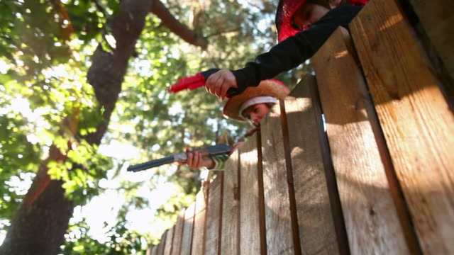 children in cowboy and cowgirl costume by wooden fence with toy weapons - toy gun stock videos & royalty-free footage