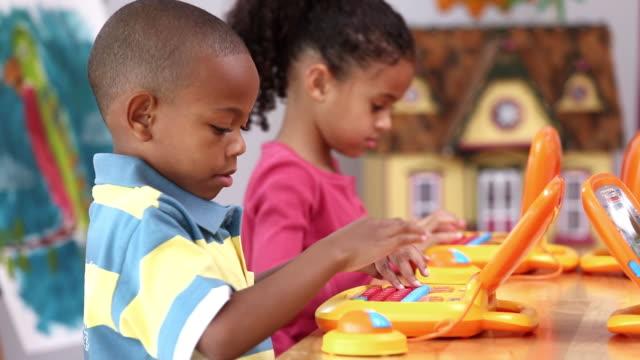 vídeos de stock e filmes b-roll de cu pan children in daycare learning how to use computers / richmond, virginia, usa - cuidar de crianças