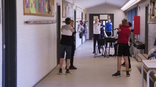 children in denmark primary school that has reopened after coronavirus lockdown hugging themselves as they have to socially distance from eachother - embracing stock videos & royalty-free footage
