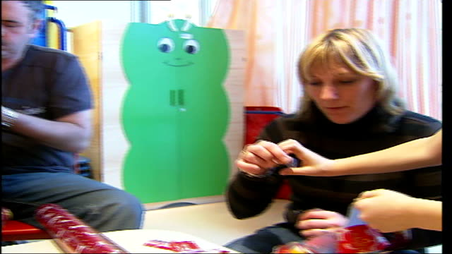 children in evelina hospital over christmas dissolve to evelina children's hospital howe family cutting up christmas wrapping paper in play area to... - christmas paper stock videos and b-roll footage