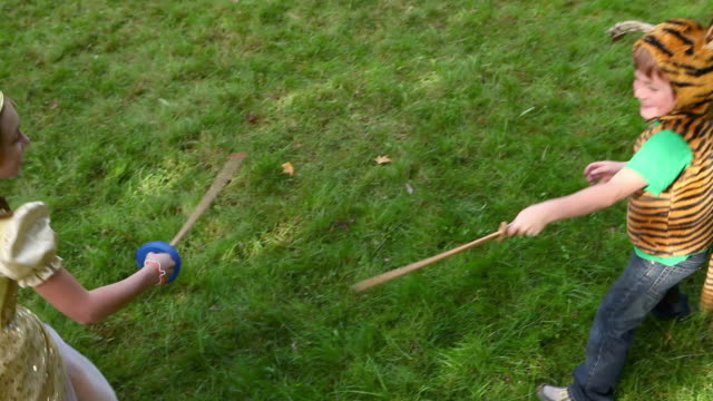 stockvideo's en b-roll-footage met children in fancy dress playing with toy swords - zwaard