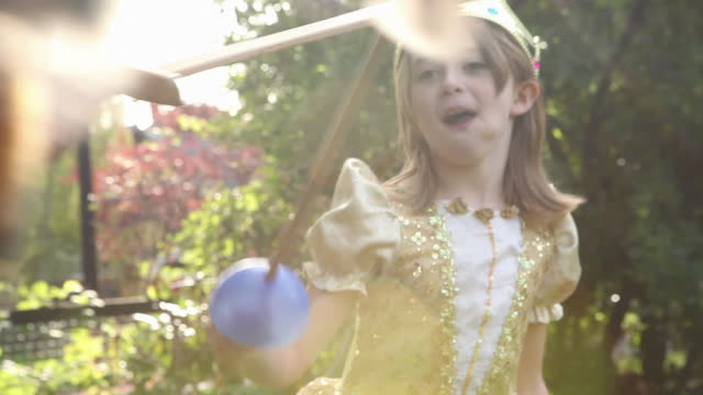 vídeos de stock e filmes b-roll de children in fancy dress playing with toy swords - princesa