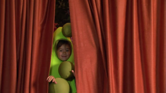 vídeos y material grabado en eventos de stock de children in food costumes peeking at camera from behind stage curtain / los angeles, california - vestuario teatral