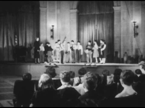 / children in front of large statue / shot of large audience and stage play-presentation / reverse shot of audience clapping / close shots of people... - anno 1951 video stock e b–roll