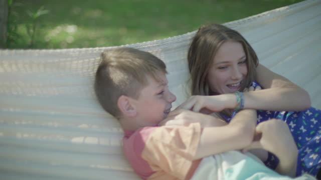 children in hammock together - auf dem rücken liegen stock-videos und b-roll-filmmaterial
