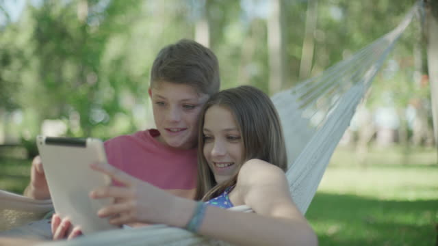 children in hammock using digital tablet together - digital native stock videos & royalty-free footage