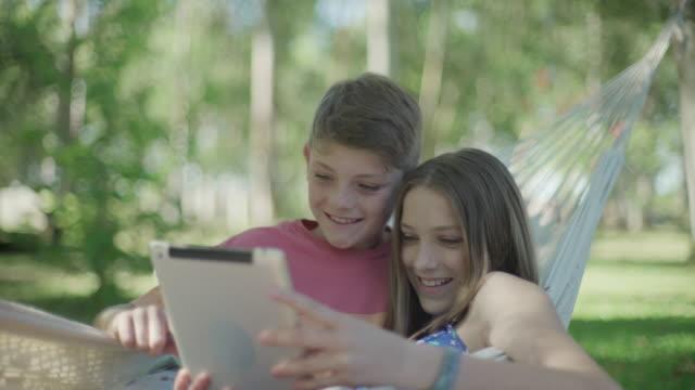children in hammock using digital tablet together - auf dem rücken liegen stock-videos und b-roll-filmmaterial