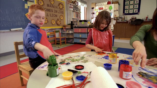 MS Children (5-6) in kindergarten painting with finger paints, Oshkosh, Wisconsin, USA