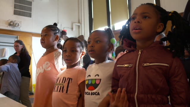 Children in Milwaukee which has come under scrutiny for de facto racial segregation in schools pledge allegiance to the USA