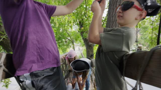 vídeos y material grabado en eventos de stock de children in pirate costumes sword fighting on tree bridge / provo, utah, united states - provo