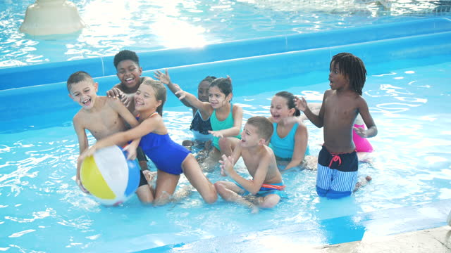 children in pool reaching up to catch a beach ball - 8 9 years stock videos & royalty-free footage