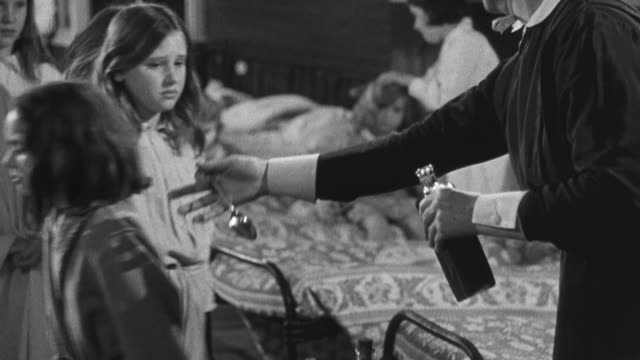 1950 recreation children in queue receiving spoonful of medicine at bedtime in a dickensian orphanage / united kingdom - orphan stock videos & royalty-free footage