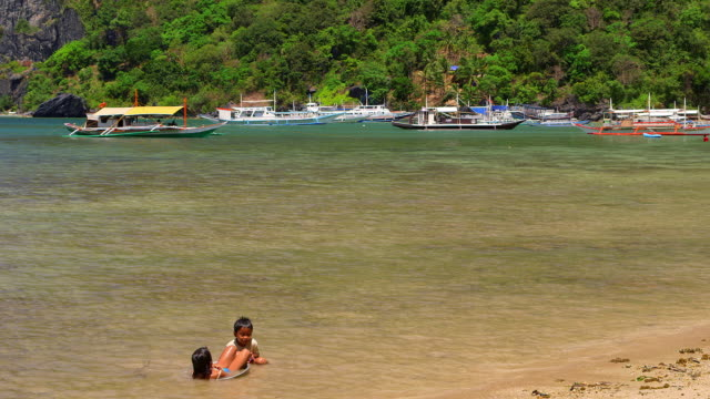 children in sea with jukung boats el nido palawan philippines no - only boys stock videos and b-roll footage