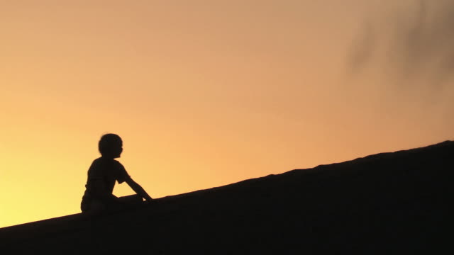 ws children in silhouette against an orange sky on a sand dune playing, throwing, and digging in the sand / san pedro de atacama, norte grande, chile - san pedro de atacama stock videos & royalty-free footage