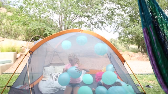 children in tent with balloons