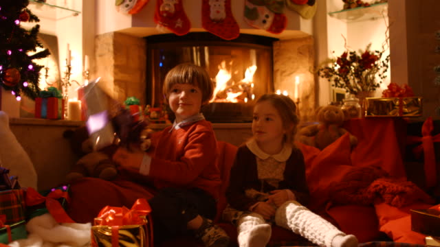 kinder in the new year's eve öffnen geschenke - socke stock-videos und b-roll-filmmaterial