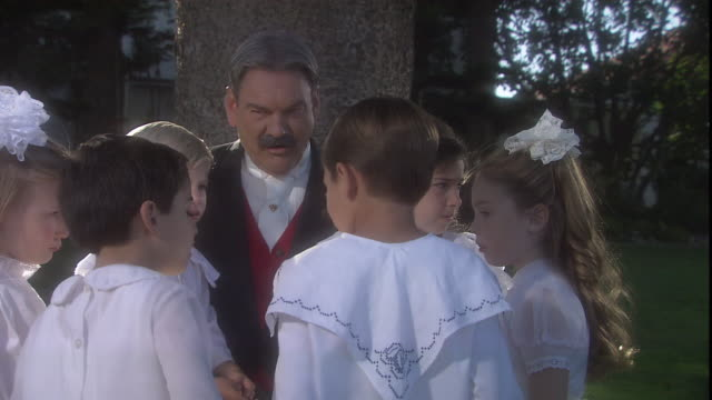 children in white clothing gather in front of a storyteller under a tree. - storyteller stock videos & royalty-free footage